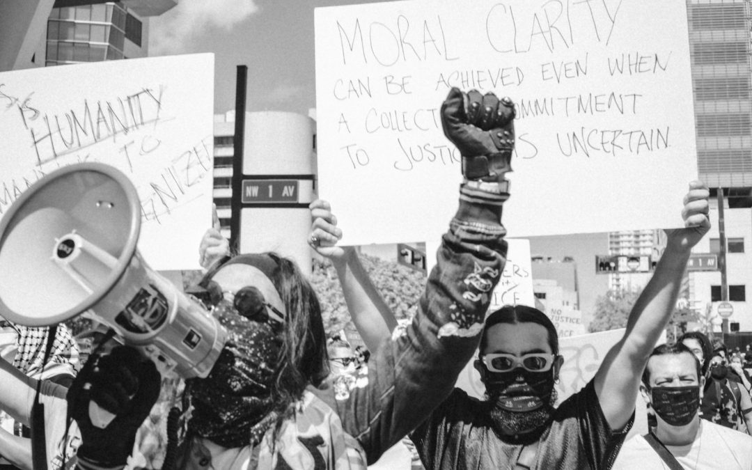 Black and white photo showing protesters with megaphone and signage for Black Lives Matter