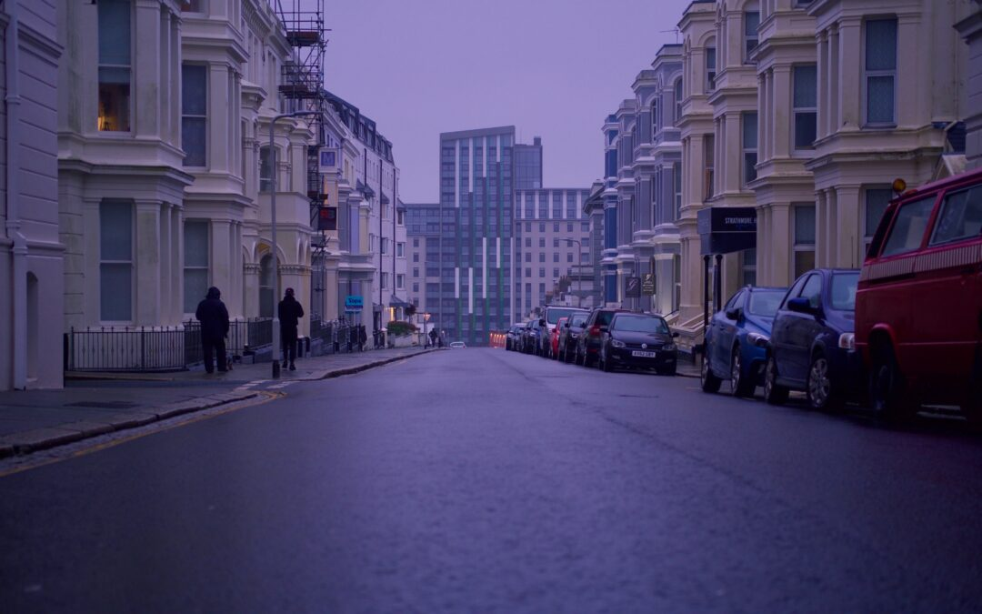 A dusk photo of a residential street with a tower block int he background